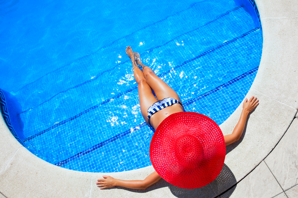 woman with sun hat by the pool