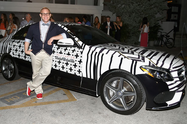 Designer Red Carter poses with a 2015 Mercedes-Benz C-Class featuring an exclusive design by Red Carter on display at the opening party celebrating 10 years during Mercedes-Benz Fashion Week Swim 2015 at The Raleigh