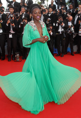 Lupita Nyong'o wearing a jade green pleated dress.