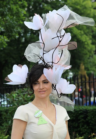 A guest at Royal Ascot in white tower hat.