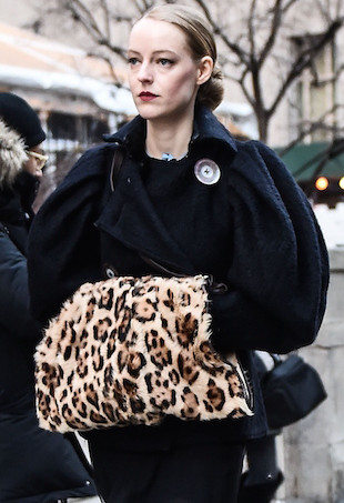 NYFW street style--a woman wearing a black dress and carrying a leopard print muff.