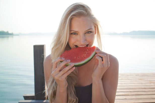 woman eating watermelon by the sea