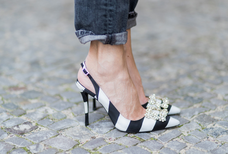 Alexandra Lapp wearing Roger Vivier pumps in a sharp cut and sheeny satin fabric in black and white stripes with crystal flower-embellished buckle at the front and sling-back shape
