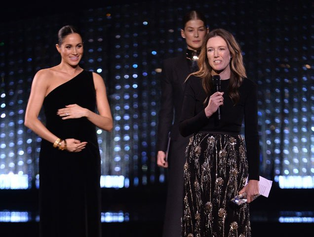 Clare Waight Keller is watched by Meghan, Duchess of Sussex and Rosamund Pike as she speaks on stage after receiving the award for British Designer of the Year Womenswear Award for Givenchy during The Fashion Awards 2018 In Partnership With Swarovski at Royal Albert Hall on December 10, 2018 in London, England.