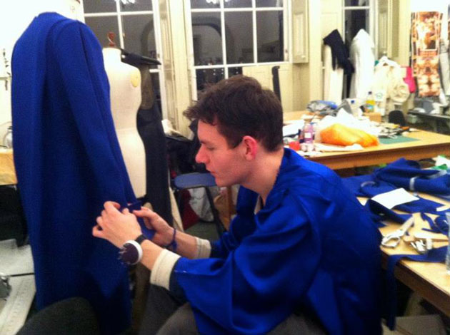 Joshua waring a silk-satin version of the coat on the mannequin, both designed by him
